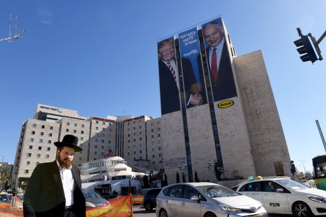 An Ultra-Orthodox Jew walks past a campaign billboard Monday showing U.S. President Donald Trump and Israeli Prime Minister Benjamin Netanyahu shaking hands, at the entrance to Jerusalem. Photo by Debbie Hill/UPI