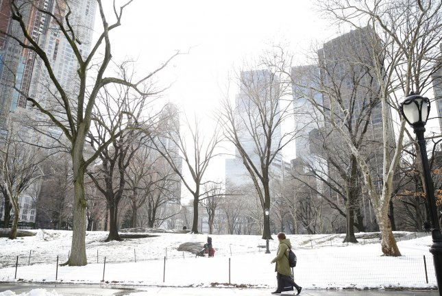 People walk through fresh snow in Central Park in New York City on April 2, 2018. The first snowtorm of the season is forecast to hit the city by midweek. File Photo by John Angelillo/UPI