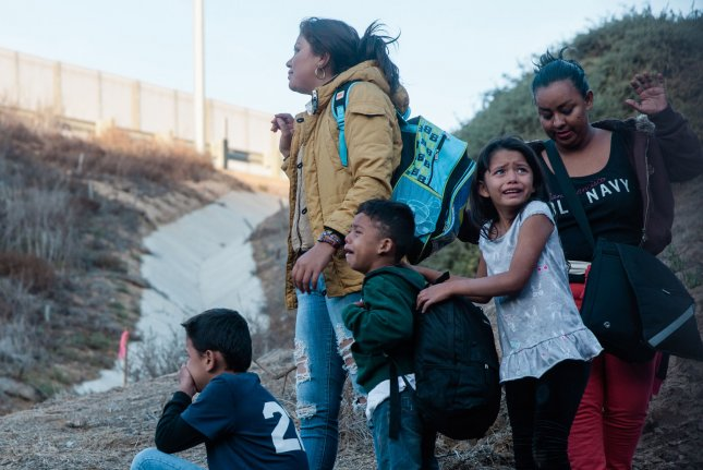 A migrant family looks at the border fence that divides the United States and Mexico near Las Playas de Tijuana, Mexico, after jumping the fence to enter the United States at San Ysidro, Calif., on December 2. Photo by Ariana Drehsler/UPI