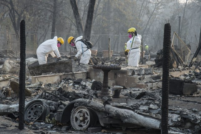 Members of the Mendocino County Sheriff's Department Search and Rescue rake through ruins in Paradise, Calif., on November 17. State fire officials blamed the blaze on PG&E. File Photo by Terry Schmitt/UPI