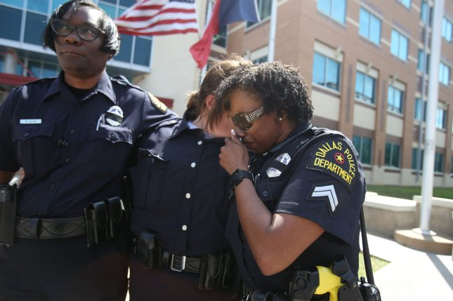 An officer gets emotional while standing outside Dallas Police Headquarters on Friday in Dallas. Four DPD officers and one DART officer were killed and seven others were wounded after a sniper opened fire during a peaceful Black Lives Matter march late Thursday. Photo by Chris McGathey/UPI