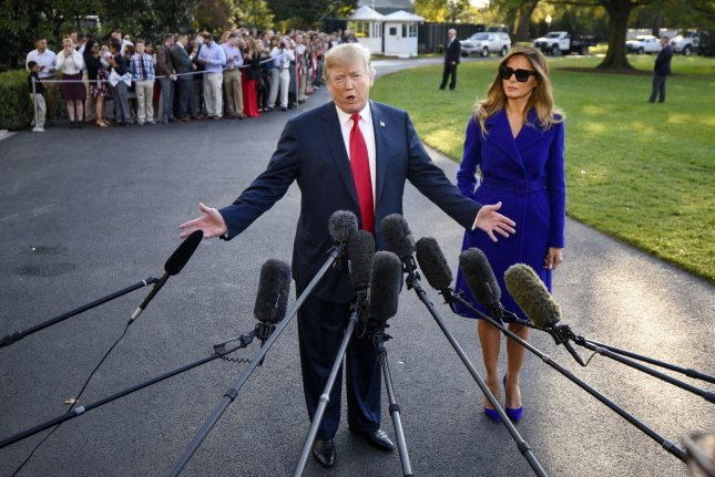 President Donald Trump answers questions from reporters Friday on the South Lawn of the White House, as first lady Melania Trump looks on. Photo by Leigh Vogel/UPI