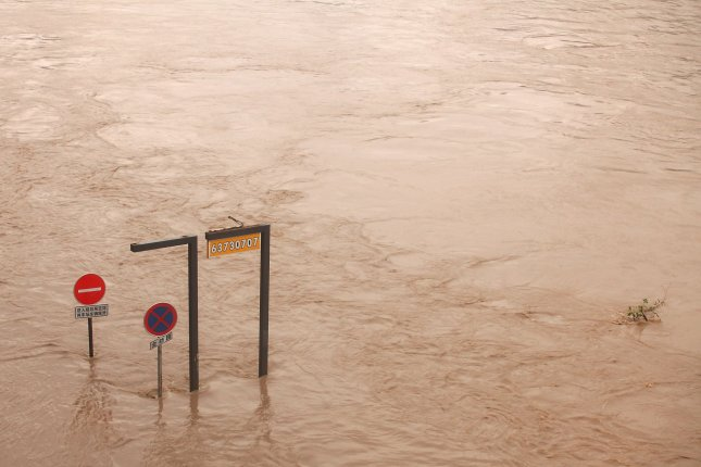 Road signs partly vanish under a swollen Yangtze River in Chongqing on August 24, 2010. The flooding from torrential summer rains, which has killed at least 700 people and displaced millions, was the worst China had suffered in more than a decade. Photo by UPI/Stephen Shaver