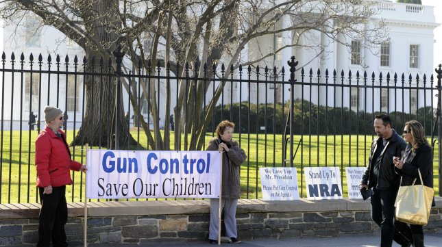 Tom Harvey (L) and his wife Pat Powers, of Rockville, Maryland, hold a gun control banner in front of the White House, December 15, 2012, in Washington, DC, in the aftermath of the shooting rampage at Sandy Hook Elementary School in Newtown, Connecticut, that left 26 dead, including 20 children. The gunman, Adam P. Lanza, 20, killed himself at the scene. UPI/Mike Theiler