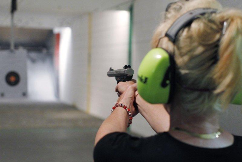A woman firing a gun at an indoor shooting range. (File/UPI/Brian Kersey)
