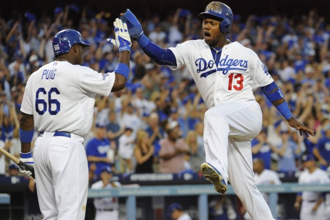 Los Angeles Dodgers shortstop Hanley Ramirez (13) high fives Los Angeles Dodgers right fielder Yasiel Puig (66) after scoring a run in the 3rd inning of Game 3 of the National League Division Series against the Atlanta Braves at Dodger Stadium in Los Angeles on October 6, 2013. The Dodgers won 13-6 to lead the best-of five NLDS 2-1. UPI/Lori Shepler