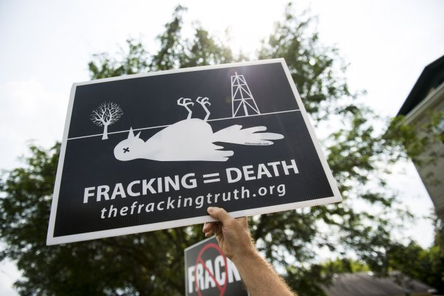 A demonstrator holds a sign during a protest against fracking in Syracuse, New York. UPI/Kevin Dietsch