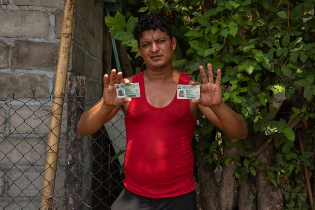 Brayan Rosales Hidalgo from Honduras holds his and his son Antony's regional visitor visa cards -- valid only for southern Mexico -- near a makeshift detention center in Mapastepec, Mexico, on Tuesday. Photo by Ariana Drehsler/UPI