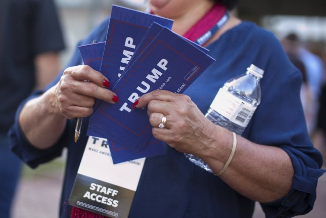 A campaign worker for then-Republican presidential candidate Donald Trump hands out information before a town hall meeting at Pinkerton Academy in Derry, N.H., on August 19, 2015. File Photo by Matthew Healey/UPI