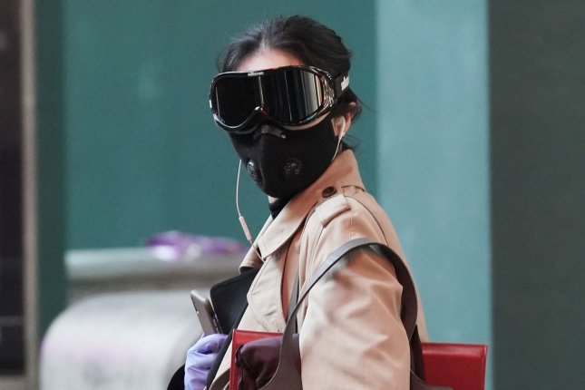 A woman walks through Times Square wearing protective goggles, latex gloves and a face mask in New York City in April 2020. File Photo by John Angelillo/UPI