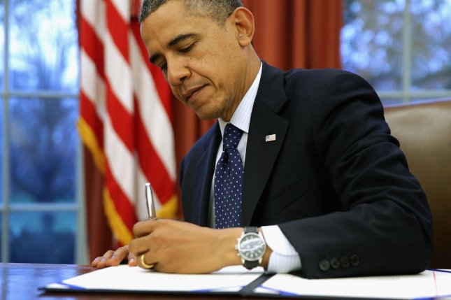 U.S. President Barack Obama signs three bills into law on the Resolute Desk inside the Oval Office at the White House November 27, 2013 (File/UPI/Chip Somodevilla/Pool)