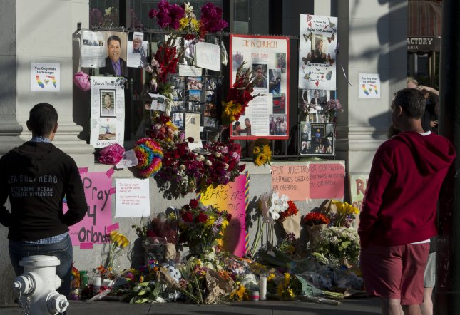 People pause at a memorial to the Orlando shooting victims Sunday in the Castro District in San Francisco. Thousands attended a candle light vigil in the city. Photo by Terry Schmitt/UPI
