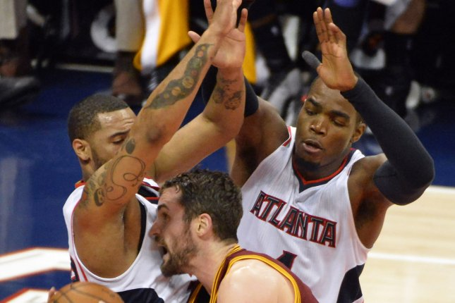 Cleveland Cavaliers forward Kevin Love (C) is blocked by Atlanta Hawks' Mike Scott (L) and Paul Millsap (R) during the first half of their NBA game at Philips Arena in Atlanta, December 30, 2014. UPI/David Tulis