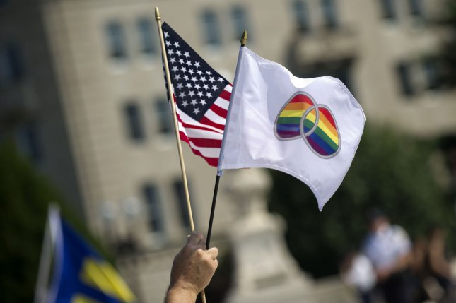 A person holds flags in front of the Supreme Court in Washington, D.C on, June 26, 2013. A federal judge on Friday struck down Alabama's same-sex marriage ban. File photo by Kevin Dietsch/UPI.