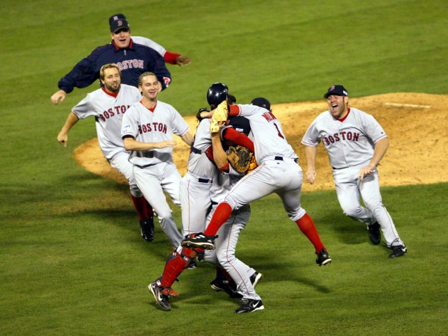 Members of the Boston Red Sox celebrate after the final out of Game 4 of the World Series beating the St. Louis Cardinals 3-0 at Busch Stadium in St. Louis on October 27, 2004. Boston took the World Championship for the first time since 1918. File Photo by Bill Greenblatt/UPI