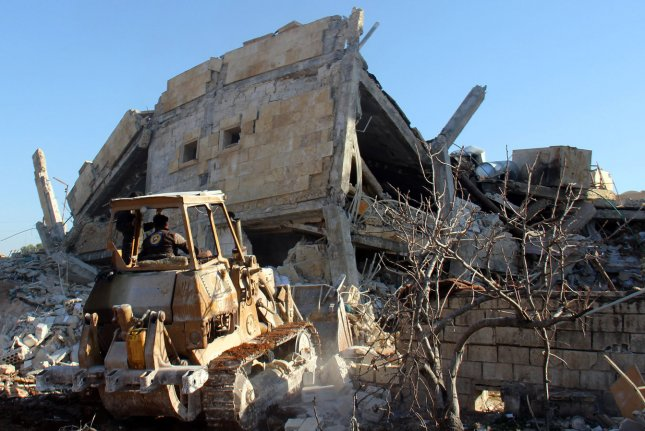A bulldozer removes debris from a bombed hospital near Maaret al-Numan, Syria. Government troops have recaptured the city, which had been a key opposition stronghold, officials said Wednesday. File Photo by Omar Haj Kadour/ UPI