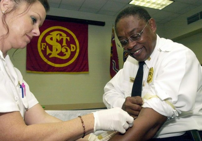 ST. LOUIS (UPI) -- St. Louis Fire Commissioner and Chief Sherman George, rolls his sleeve up for paramedic Donna Lowe as she performs a Hepatitis C test at St. Louis Fire Department Headquarters in St. Louis on Sept. 9, 2002. The St. Louis Fire Department is the first fire department in the U.S. to test all firefighters and paramedics for the blood-borne virus that is transmitted by direct exposure to contaminated blood. Hepatitis C has reached epidemic proportions among emergency workers in recent years. jg/bg/Bill Greenblatt UPI
