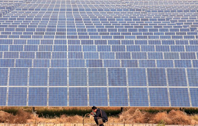 A Chinese man talks on his phone next to a solar panel field operating in the Taiyangshan Development Zone in Wuzhong, a frontier city in the northwestern province Ningxia Hui Autonomous Region on September 22, 2011. The 215 square mile zone has the advantages of both strong wind and solar power, resulting in 300 megawatts of wind power and 100 megawatts of photovoltaic power. Taiyangshan is the biggest clean energy base in China. UPI/Stephen Shaver