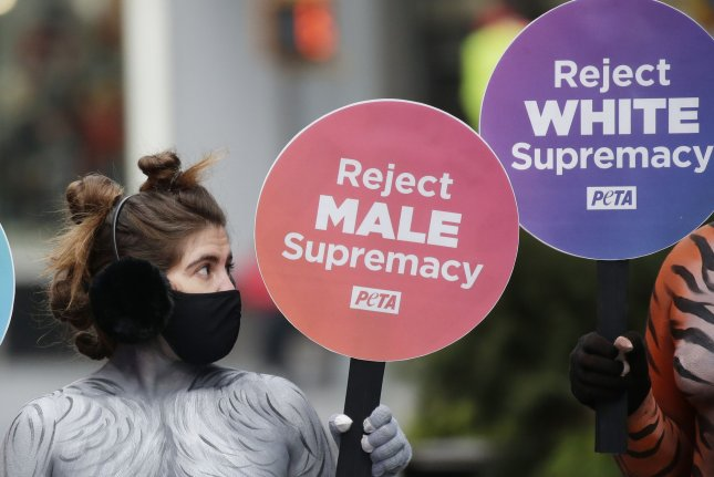 Activists wearing body paint hold signs against White and male supremacy in New York City's Times Square on December 8, 2020. The demonstration also opposed heterosexual supremacy and human supremacy. File Photo by John Angelillo/UPI