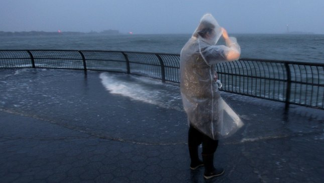 A woman watches the water spill over into Manhattan in Battery Park in New York City on October 29, 2012. UPI/John Angelillo