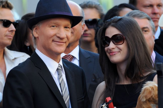 Real Time host Bill Maher (L) and girlfriend Cara Santa Maria, holding dog Killer, share a light moment during an unveiing ceremony honoring him with the 2,417th star on the Hollywood Walk of Fame in Los Angeles on September 14, 2010. File Photo by Jim Ruymen/UPI