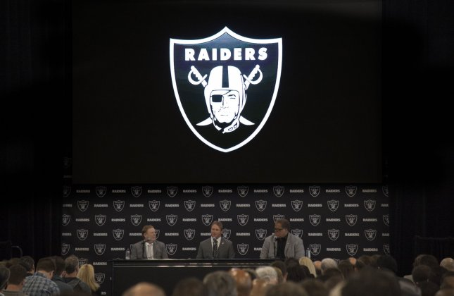 Oakland Raiders head coach John Gruden (C) answers questions with owner Mark Davis (L) and Reggie McKenzie at the Raiders Headquarters in Alameda, California in January. Photo by Terry Schmitt/UPI