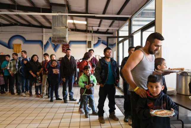 Migrants line up to receive food at a federal facility in El Paso, Texas, on March 22. File Photo by Justin Hamel/UPI