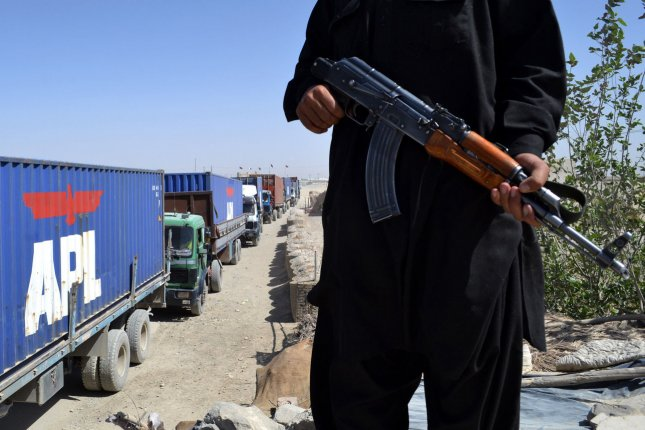 Pakistani security forces stand guard as trucks carrying NATO and U.S. military vehicles from U.S. base in Kandahar, Afghanistan cross the border at Chaman, Pakistan to the port of Karachi on September 2, 2013. The present 70,000 U.S. Troops will be cut to 34,000 by February 2014, but the NATO commander Lt. Gen. Mark Milley said on September 4, 2013, that there has been no discussions that the coalition would completely withdraw by the end of 2014. UPI/Matiullah