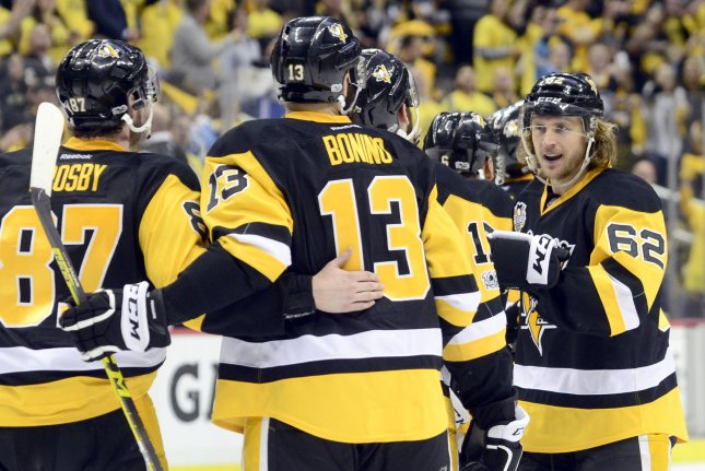 Pittsburgh Penguins left wing Carl Hagelin (62) joins Pittsburgh Penguins center Nick Bonino (13) and Pittsburgh Penguins center Sidney Crosby (87) in celebrating following the Pittsburgh Penguins' 3-2 double overtime win against the Ottawa Senators of game seven to win the Eastern Conference Finals of the Stanley Cup Playoffs at PPG Paints Arena. File photo by Archie Carpenter/UPI