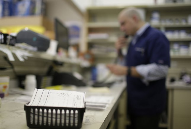 A pharmacist talks on the phone near a basket of prescriptions in the pharmacy department of a New York State pharmacy on March 21, 2016.In Canada on Thursday, Quebec officials announced they would offer to the public free naloxone, a drug used to counter the effects of opioid overdoses. The drug will be available in pharmacies free of charge. File Photo by John Angelillo/UPI