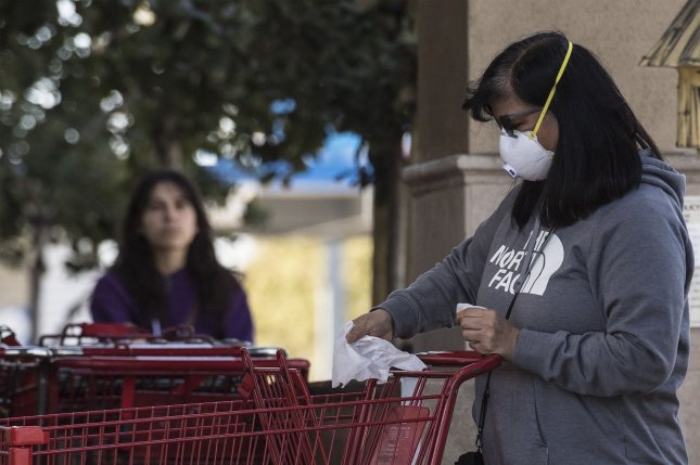 A customer wearing an N95 face mask wipes down s shopping cart with disinfectant wipes at a Trader Joe's in Los Altos, California in this April photo. The CDC is investigating a salmonella outbreak that has sickened people in 23 states, but it has not yet determined the source of contamination. Photo by Terry Schmitt/UPI