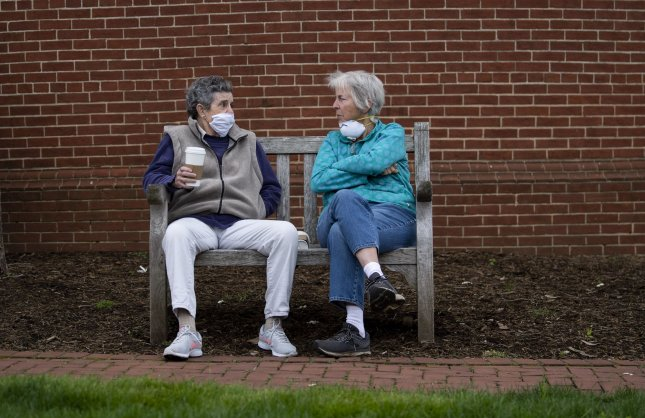 People wears masks as they sit on a bench in downtown Annapolis, Md., amid the COVID-19 pandemic on Monday. Photo by Kevin Dietsch/UPI