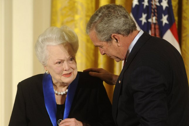 President George W. Bush (R) presents Olivia De Havilland with the 2008 National Medals of Arts at the White House in 2008. She died this weekend at age 104. File Photo by Kevin Dietsch/UPI