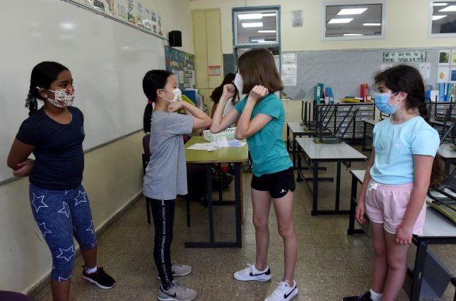 Effective testing and contact tracing is the only way to open schools and limit spread of COVID-19, researchers say. Pictured, students in Israel wear protective masks as they return to the Yankus Korchak Elementary School in Jerusalem in May. Photo by Debbie Hill/UPI
