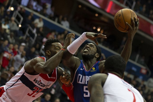 Los Angeles Clippers forward Montrezl Harrell (5) drives to the basket while defended by Washington Wizards forward Jeff Green (32) and guard John Wall (2) at Capitol One Arena in Washington, DC. Photo by Alex Edelman/UPI