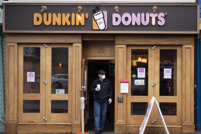 A man wears a mask as he leaves a Dunkin' Donuts store in downtown Annapolis, Md., earlier this year. File Photo by Kevin Dietsch/UPI