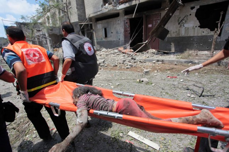 Medics evacuate the body of a girl from Gaza's eastern Shejaiya district on July 20, 2014. (UPI/Ashraf Mohamad)