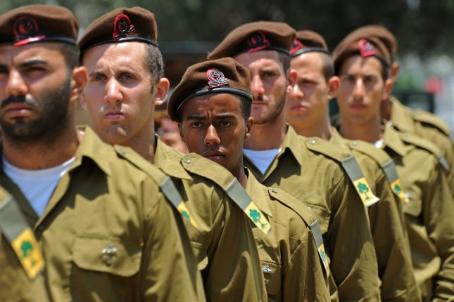 An Israeli military honor guard waits for the arrival of the flag covered coffin of Major Tsafrir Baror, 32, for his military funeral in the Holon cemetery, Israel, July 21, 2014. Baror, an officer in the Golan Brigade,was killed by Palestinian militants in Gaza. He leaves behind a wife, Sivon, who is eight months pregnant and a year old daughter. The Israel Defense Force says it has lost 18 soldiers, while more than 508 Palestinians have been killed in the 14 day battle. UPI/Debbie Hill