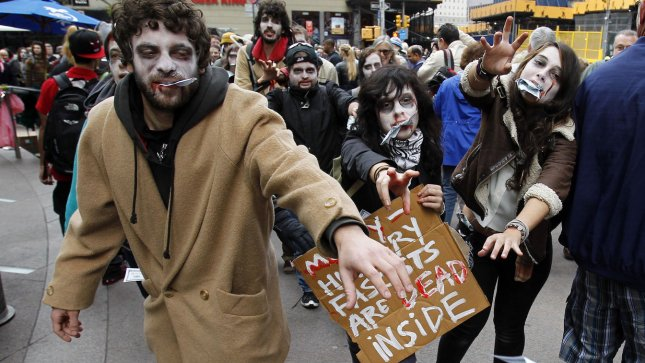 Wall Street Protestors dressed as zombies hold up signs as the walk to the New York Stock Exchange after the opening bell on Wall Street In New York City on October 3, 2011. UPI/John Angelillo