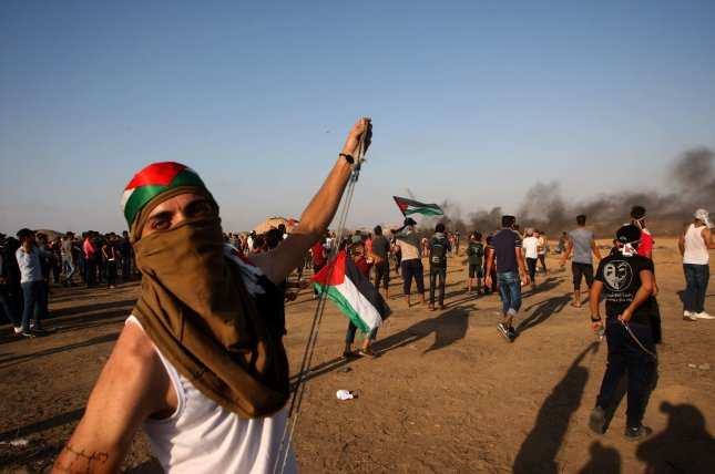A Palestinian man uses a slingshot to hurl stones during clashes between Palestinian protesters and Israeli forces along the border on Friday. Photo by Ismael Mohamad/UPI
