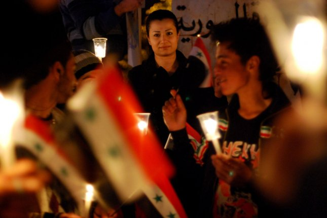 Anti-government protesters hold the Syrian flags and candles at Shuhada or (Martyrs) Square in Swaeda in Daraa, Syria, on March 28, 2011. Syrian forces captured the city away from rebels Thursday. File Photo by Ali Bitar/UPI