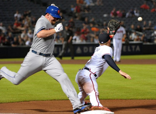 Atlanta Braves first baseman Freddie Freeman (R) stretches to force out New York Mets' John Buck on the infield grounder during the fourth inning at Turner Field in Atlanta, June 17, 2013. UPI/David Tulis