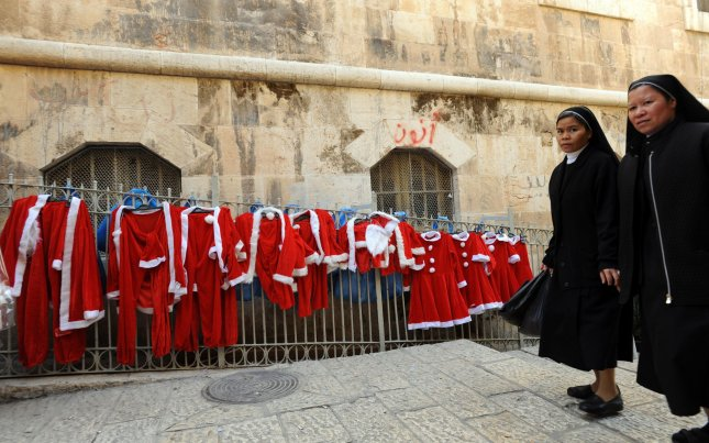 Nuns walk past a row of Santa Claus costumes displayed outside a shop in the Old City of Jerusalem, December 22, 2010. UPI/Debbie Hill