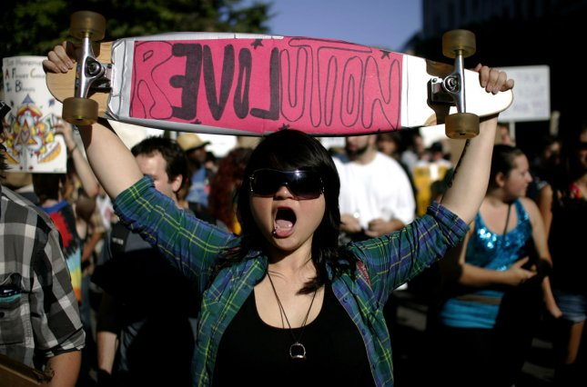 A protester with the Occupy Boston movement holds a skateboard over her head while marching on Boylston Street in Boston, Massachusetts on October 8, 2011. The group has been occupying Dewey Square in Boston for over a week now. UPI/Matthew Healey