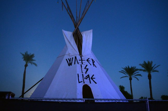 A teepee with the message Water is Life, referring to the Dakota Access pipeline protest is seen as Neil Young performs onstage during Desert Trip 2 at the Empire Polo Field in Indio, Calif. on October 15. Federal decision halts construction of the last few hundred feet of the controversial oil pipeline. File Photo by Jim Ruymen/UPI