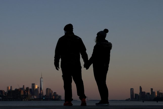 A couple hold hands in West New York, N.J., on Wednesday with the Manhattan skyline in the background. Photo by John Angelillo/UPI