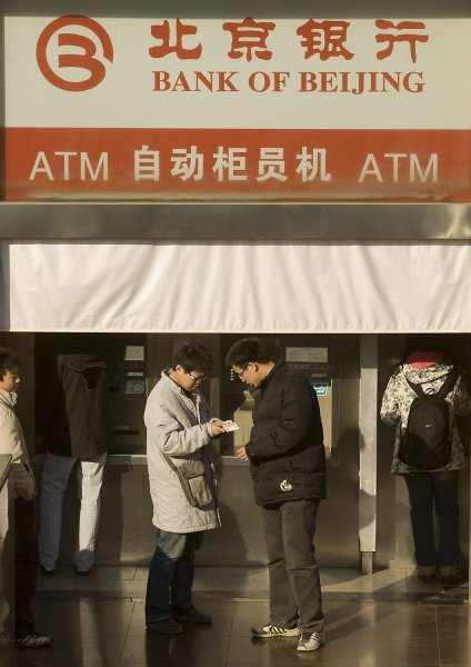 Two Chinese men examine their ATM receipt outside a 24-hour Bank of Beijing ATM service center in downtown Beijing January 13, 2009. (UPI Photo/Stephen Shaver)