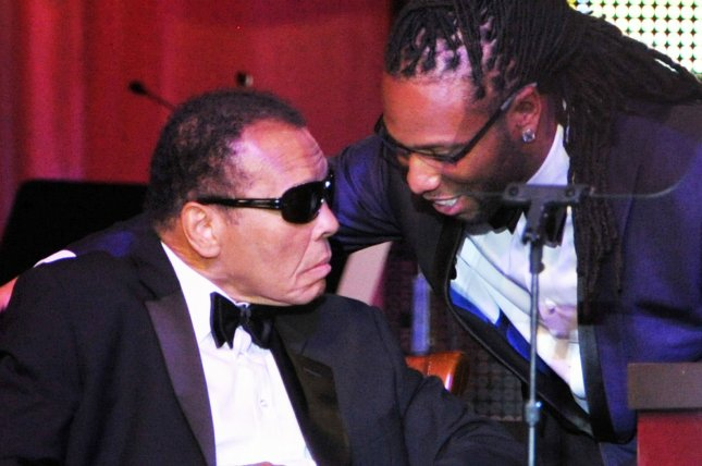 Arizona Cardinals wide receiver Larry Fitzgerald (R) speaks to Muhammad Ali on stage at the Muhammad Ali Celebrity Fight Night. UPI/Art Foxall