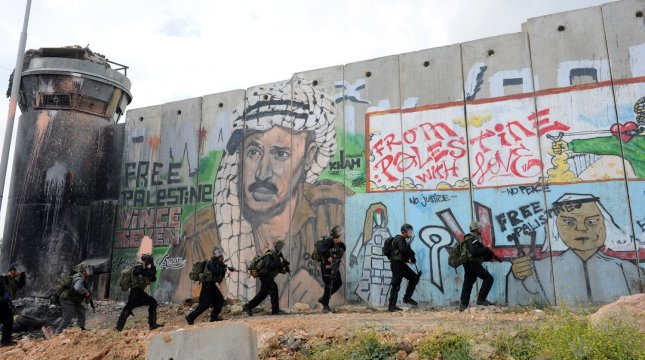 Israeli soldiers take position beside the Israeli separation wall at the Qalandiya Checkpoint, West Bank, as Palestinians protesters, not seen, march on Nakba, Arabic for Catastrophe, the term used to mark events leading to the founding of Israel, May 15, 2011. Nakba Day is the annual day of protests by Palestinians marking the creation of the State of Israel in 1948. UPI/Debbie Hill