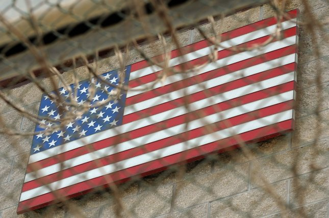 An American Flag is seen through chain link fence and razor wire at Camp VI in Camp Delta at Naval Station Guantanamo Bay in Cuba. UPI/Roger L. Wollenberg